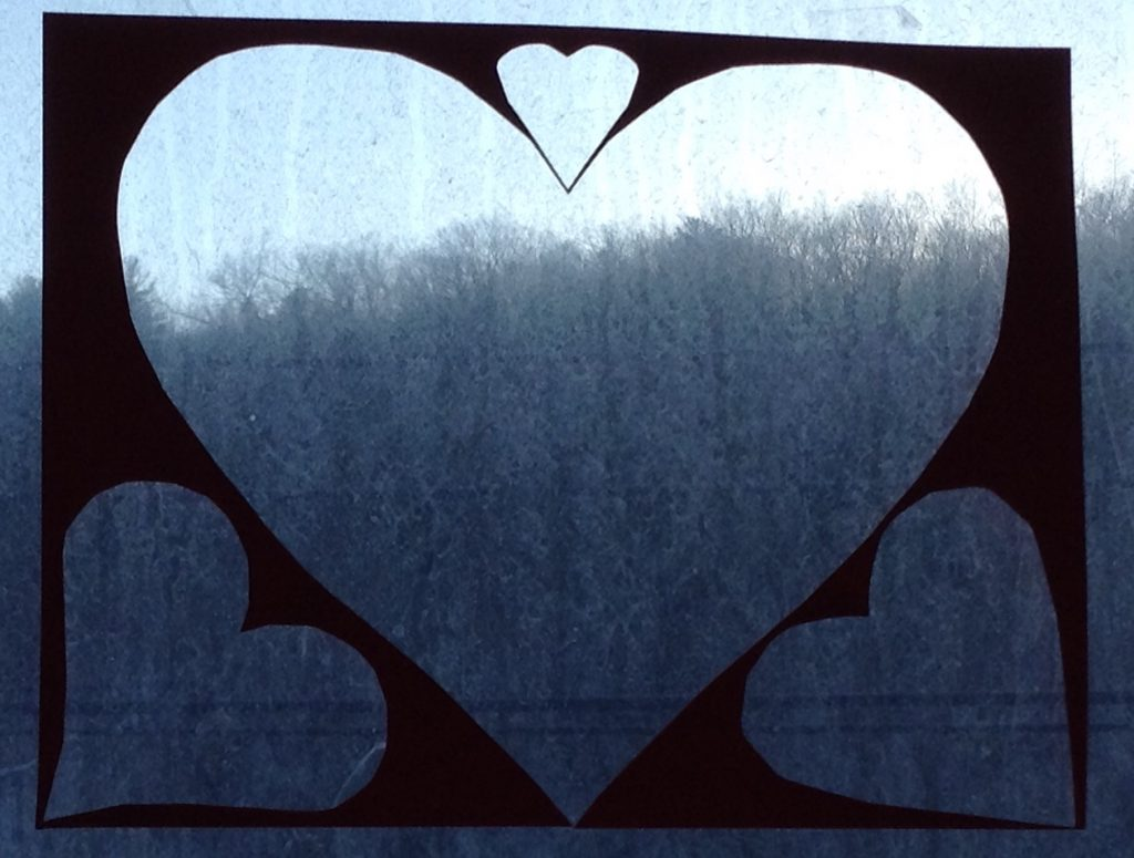 Grey sky, winter landscape through hearts
